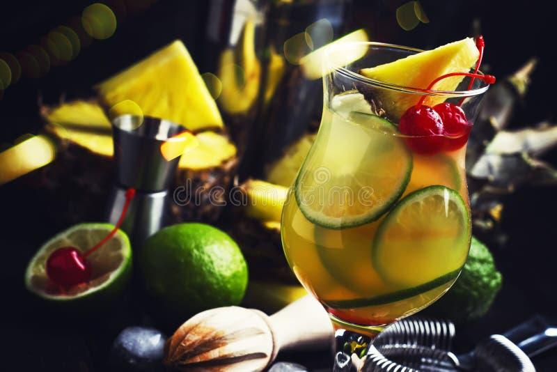 Exotisk stansmaskincoctail för sommar med ananasfruktsaft, limefrukt, is och vodka, räknarebakgrund för grå stång, bartenderhjälp royaltyfri bild