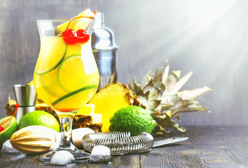 Exotisk stansmaskincoctail för sommar med ananasfruktsaft, limefrukt, is och vodka, räknarebakgrund för grå stång, bartenderhjälp fotografering för bildbyråer