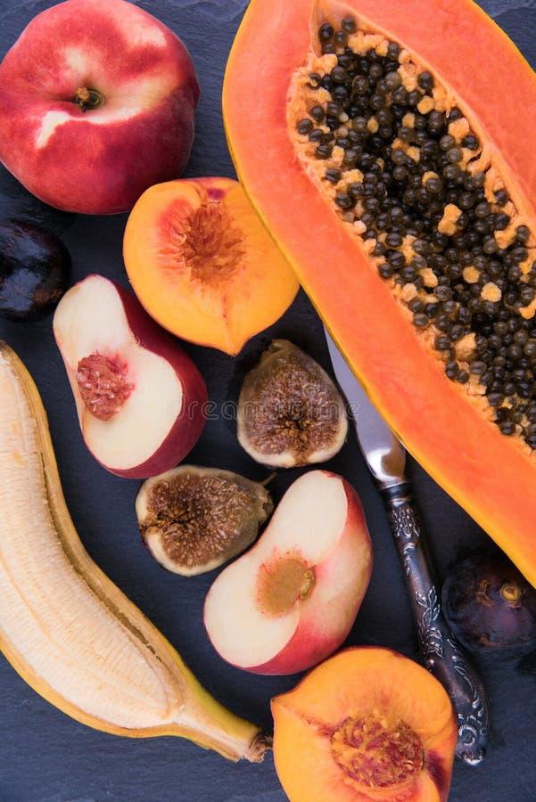 Exotisk stilleben för fruktvariation på tappningstenbräde med kniven royaltyfria foton
