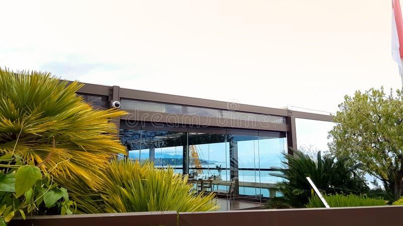 Exotisk trädgård och restaurang i det lyxiga hotellet, Monaco flagga som vinkar, rikt liv arkivfoton