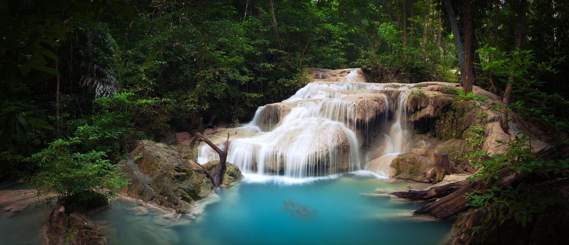 Exotisk tropisk vattenfall i grön djungelskog royaltyfri fotografi