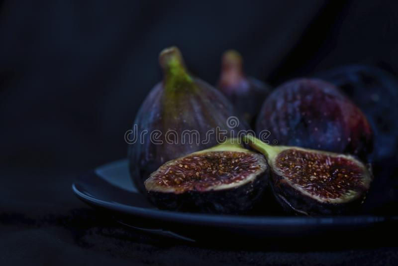 Exotiska fikonträdfrukter i en blå platta på svart bakgrund, slut upp som isoleras, stillebenfotografi fotografering för bildbyråer
