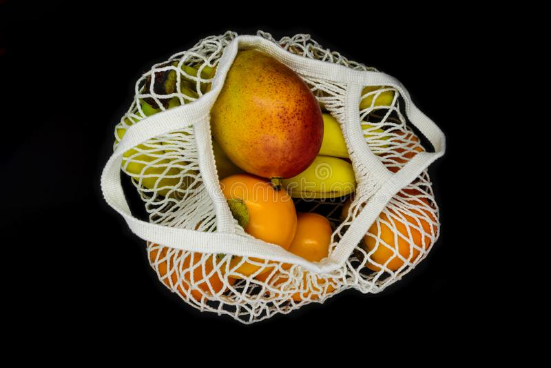 Exotiska frukter i netto påse för vitt ingrepp och som isolerar på svart bakgrund arkivfoto