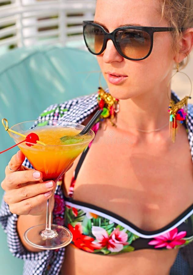 Exotiskt coctailexponeringsglas i kvinnas hand royaltyfri bild