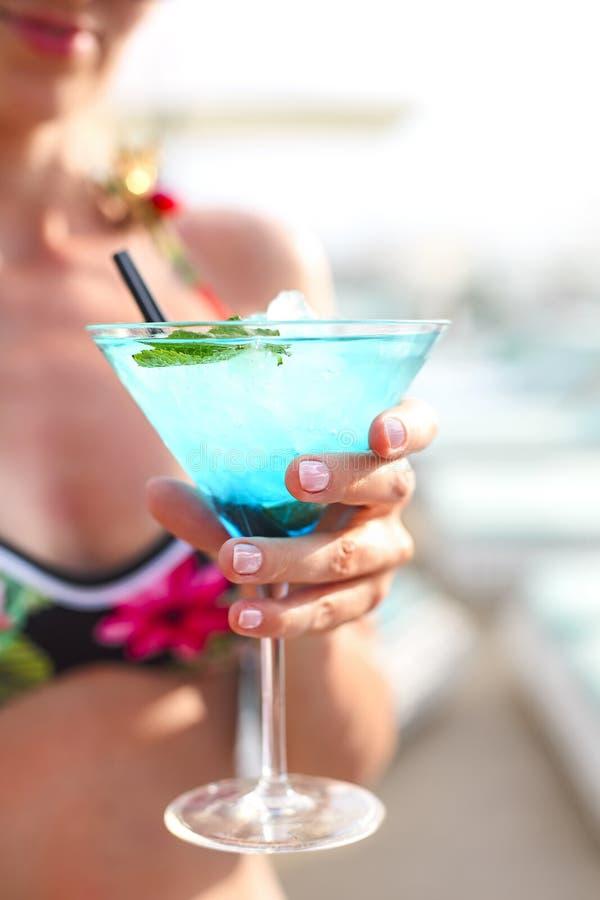 Exotiskt coctailexponeringsglas i kvinnas hand royaltyfria foton