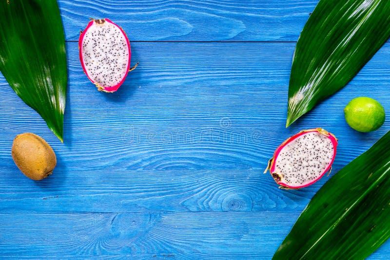 Exotiskt fruktmål Dragonfruit kiwi, limefrukt på blå träcopyspace för bästa sikt för tabellbakgrund arkivfoton