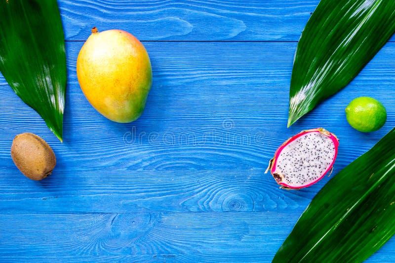 Exotiskt fruktmål Dragonfruit mango, kiwi, limefrukt på blå träcopyspace för bästa sikt för tabellbakgrund arkivfoton