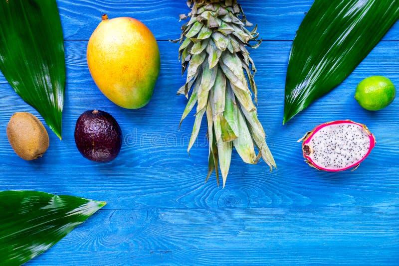 Exotiskt fruktmål Dragonfruit, mangosteen, mango, kiwi, limefrukt och ananas på blå träcopyspace för bästa sikt för bakgrund arkivfoto