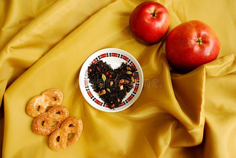 Exotiskt kinesiskt te med knoppar av en kryddnejlika, en koriander, skivor av äpplen, apelsiner, rosa peppar royaltyfri fotografi