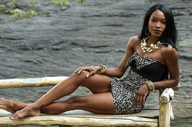 Exotiskt seende afrikansk amerikankvinnasammanträde på bänken royaltyfria foton