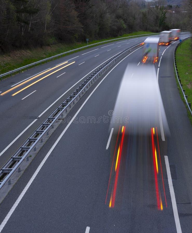 Expédiant la tache floue de mouvement des camions avec rougeoyer s'allume sur la route image libre de droits