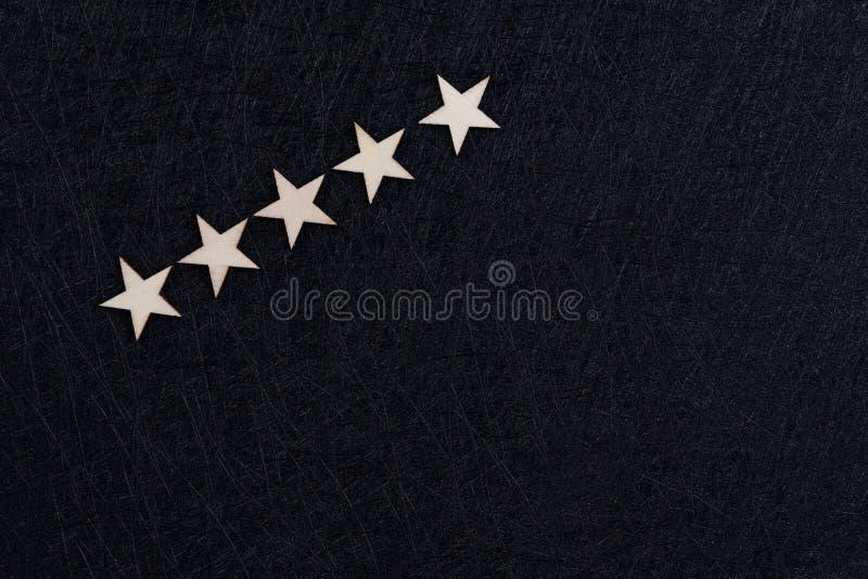 Expérience d'utilisateur, examen de client ou concept d'estimation, 5 étoiles en bois sur le fond noir foncé avec l'espace de cop photo libre de droits