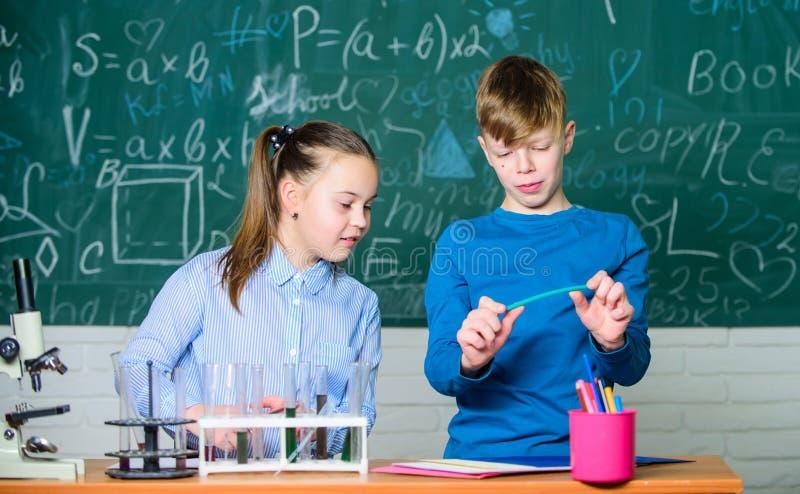 Expérience futée d'école de conduite d'étudiantes de fille et de garçon Éducation d'école Analyse chimique Chimie occupée d'étude photos stock