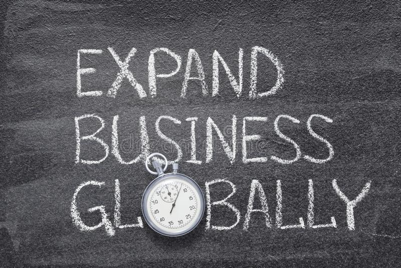 Expand business watch. Expand business globally phrase written on chalkboard with vintage precise stopwatch stock images
