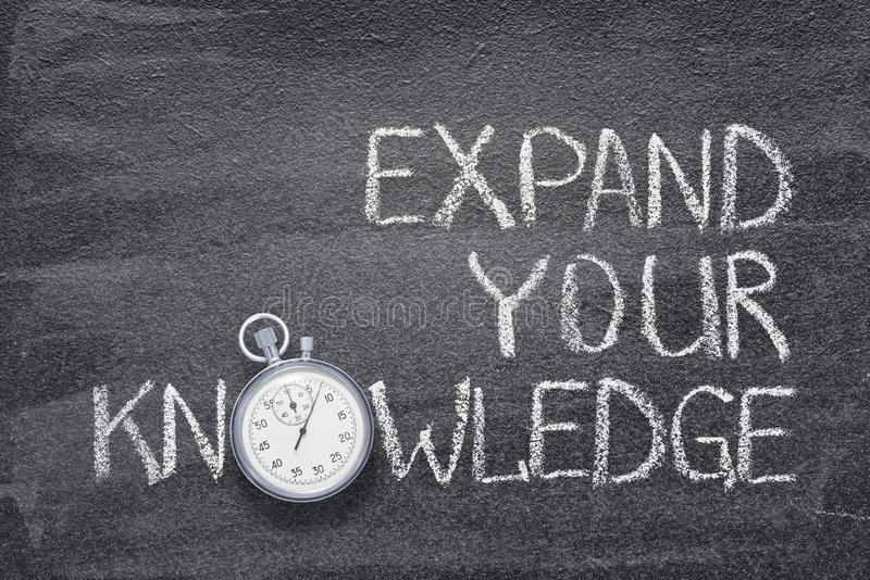 Expand knowledge watch. Expand your knowledge phrase written on chalkboard with vintage stopwatch used instead of O royalty free stock photography