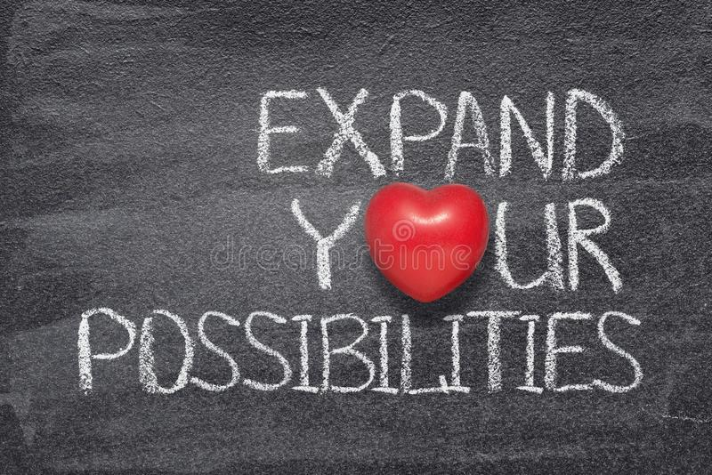 Expand possibilities heart. Expand your possibilities phrase written on chalkboard with red heart symbol instead of O royalty free stock photos