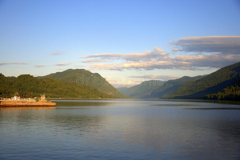 The expanse of a mountain lake at sunset under a cloudy sky, on the side part of a pier with a motor ship royalty free stock photos