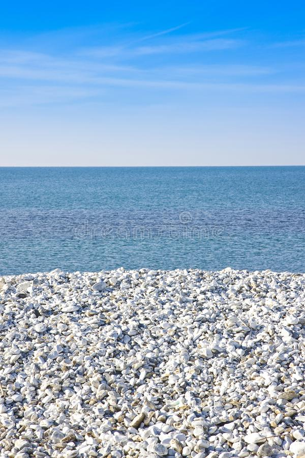 Expanse of white gravel on the sea coast with calm sea on backgr stock images