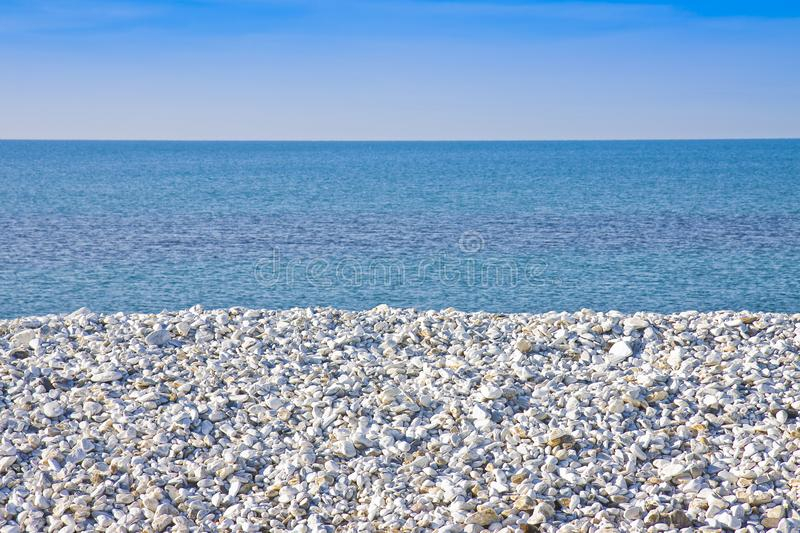 Expanse of white gravel on the sea coast with calm sea on backgr royalty free stock photography