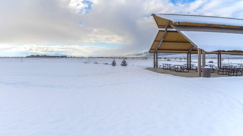 Expansivt landskap för klar panorama som filt med snö under en molnig blå himmel i vinter under arkivbilder
