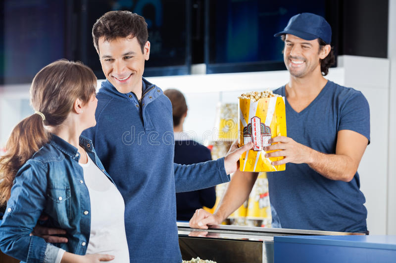 Expectant Couple Buying Popcorn At Concession. Loving expectant couple buying popcorn from male seller at concession stand in cinema stock image