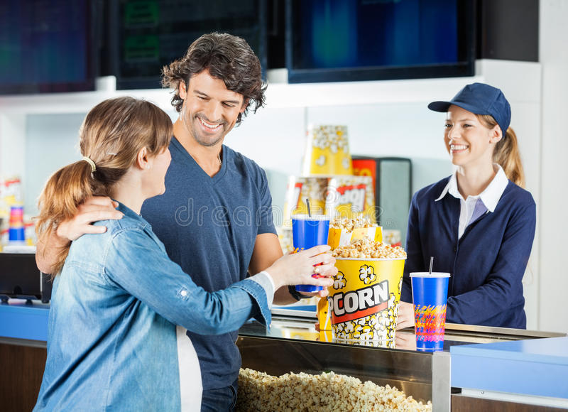 Expectant Couple Buying Snacks At Concession Stand. Happy expectant couple buying snacks from female seller at cinema concession stand stock image