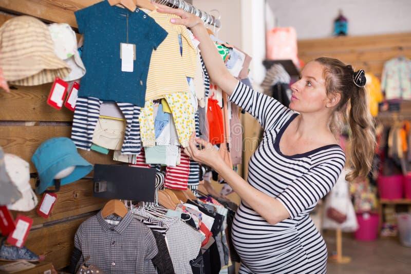 Expectant matka W pasiastej tunika zakupy sukni w sklepie odzieżowym obraz stock