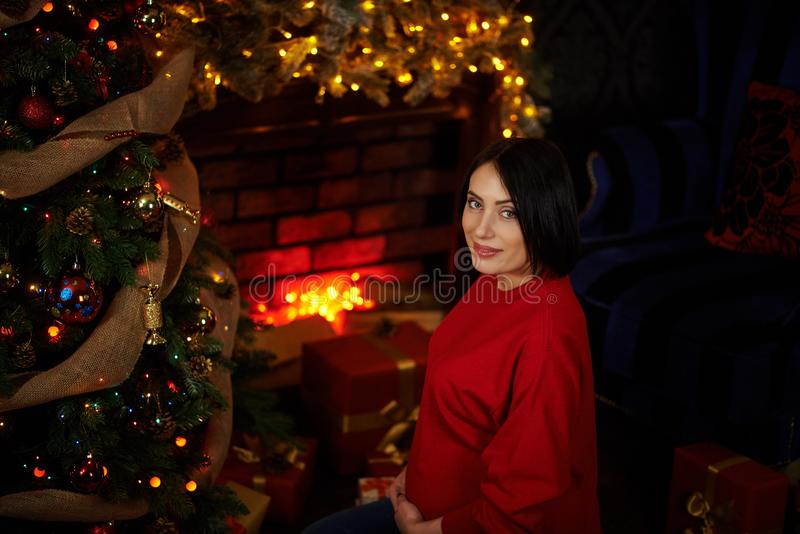 The expectant mother strokes her belly at the Christmas tree stock photography