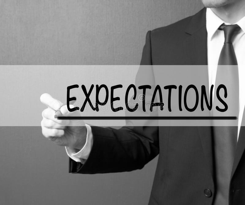 Expectations. Businessman in a suit with a marker writing on visual screen royalty free stock images