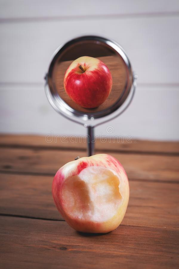 Expectations and reality concept - bitten apple with perfect mirror reflection. Expectations and reality concept - bitten red apple with perfect mirror stock photography