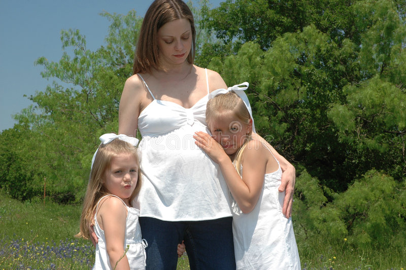 Expecting. An expectant mother holds her two daughters together as they hug the unborn child in her belly royalty free stock images