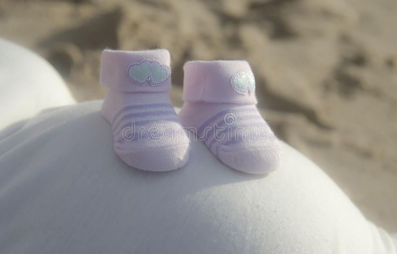Expecting a little girl. Big tummy, tiny pink shoes in anticipation of their first born royalty free stock images