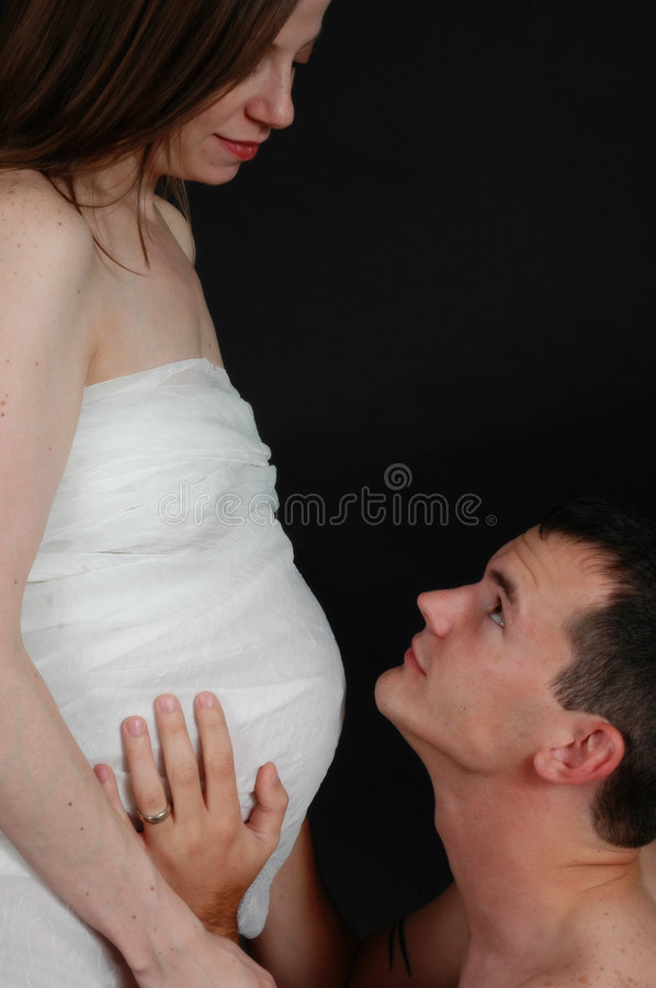Expecting Parents. Pregnant woman standing with her husband kneeling and looking at her as he holds his hands on her belly stock photography