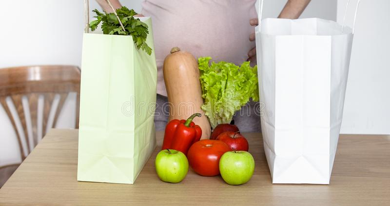 Expecting woman take out vegetables from shopping bag stock photography