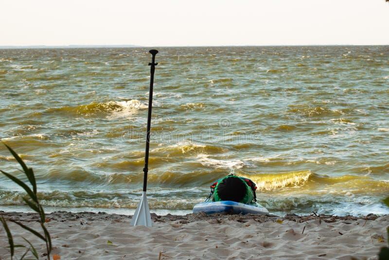 A expedição levanta-se o paddleboard, uma pá e uma placa do sup na costa, fotografia de stock royalty free