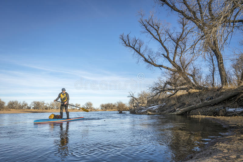 Expedition winter stand up paddling on South Platte RIver. Expedition style winter stand up paddling on the South Platte RIver in eastern Colorado royalty free stock photography