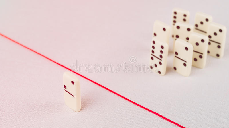 Expelled from the group, unable to cross the red line that separates them. Scene with group of domino. Concept of stock photo