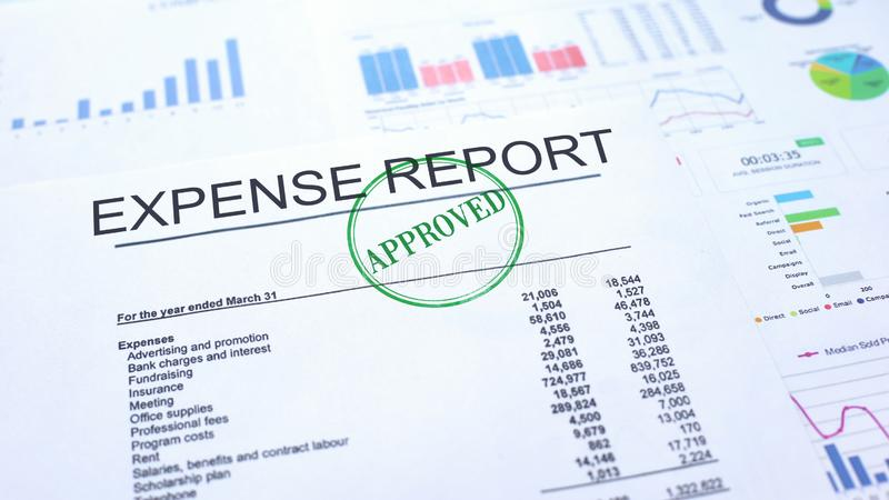 Expense report approved, hand stamping seal on official document, statistics stock image