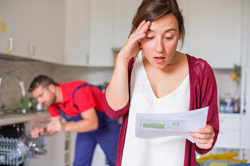 Expensive appliance repair costs and sad woman. Housewife shocked after reading repair cost estimate of domestic appliance stock photo