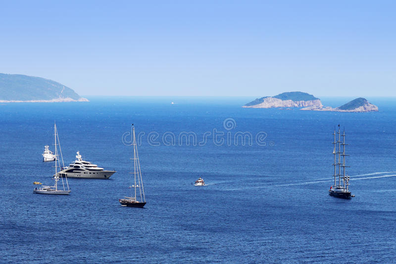 Expensive boats on large sea with island stock photography