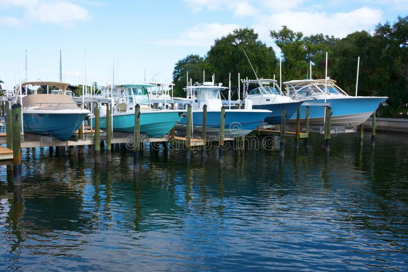 Expensive fishing boats on boat lifts at dock stock photo