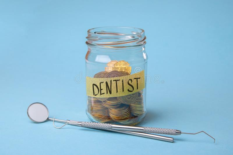 Expensive dental services. Glass jar with coins and dental instruments, mirror and probe hooks.  stock photos
