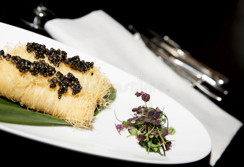 Expensive dish with black caviar royalty free stock image