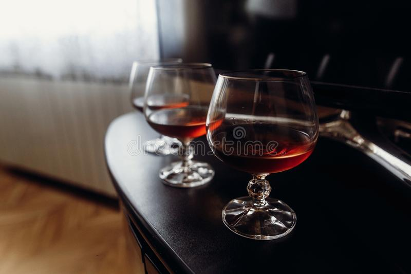 Expensive glasses with whiskey on dark wooden table closeup, cognac drinks in glasses on black background, morning wedding royalty free stock photography
