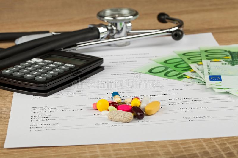 Expensive healthcare. Close up picture of medical insurance document, pills, calculator and money - Healthcare costs royalty free stock photo