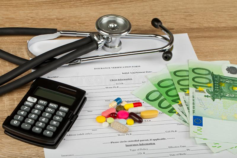 Expensive healthcare. Close up picture of medical insurance document, pills, calculator and money - Healthcare costs stock photo