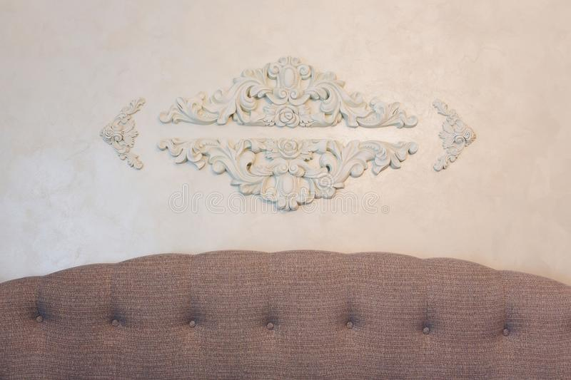 Expensive interior. Stucco elements on light luxury wall. White patterned. Mouldings element from gypsum. Roccoco style. royalty free stock photography