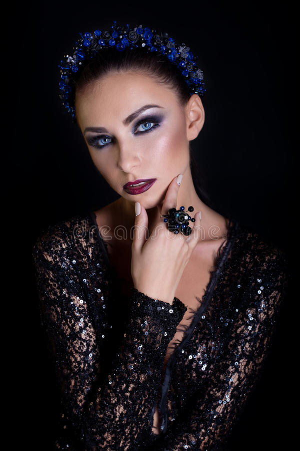 Expensive jewelry wreath earrings and ring on a beautiful elegant brunette girl with a bright evening make-up in a black even. Ing dress with lace stock photos