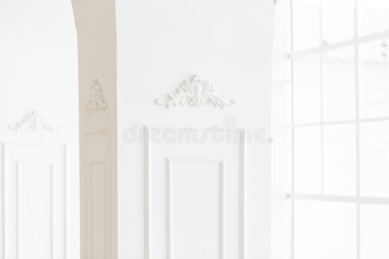 Expensive luxury interior. Stucco elements on line of light columns. White patterned. Mouldings element from gypsum.  royalty free stock photos
