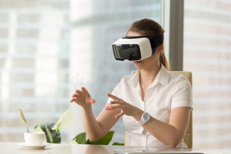 Experiência dos auriculares de VR, óculos de proteção vestindo da mulher curiosa que tocam em vi fotografia de stock